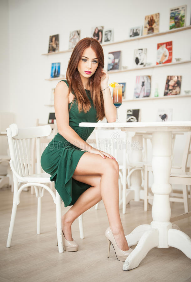 Jovem mulher atrativa elegante no vestido verde que senta-se no restaurante fotografia de stock