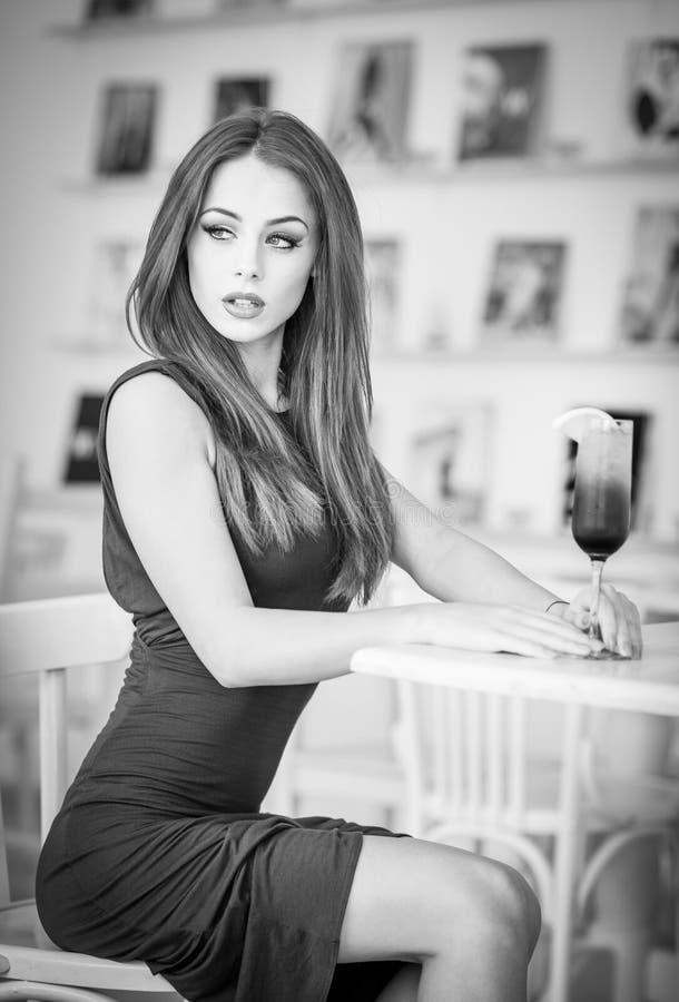 Jovem mulher atrativa elegante no vestido verde que senta-se no restaurante imagem de stock royalty free