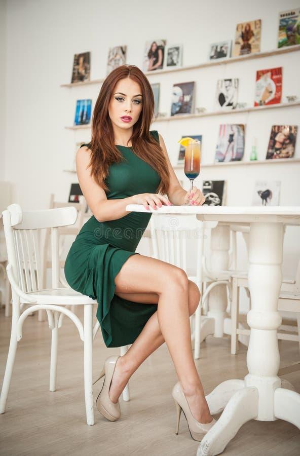 Jovem mulher atrativa elegante no vestido verde que senta-se no restaurante foto de stock