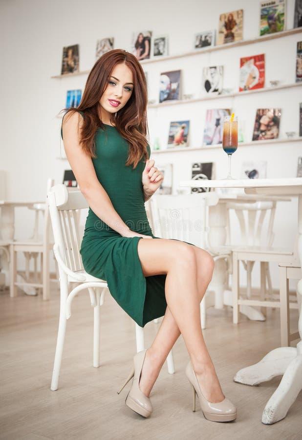 Jovem mulher atrativa elegante no vestido verde que senta-se no restaurante Ruivo bonito que levanta no cenário elegante com suco imagens de stock royalty free