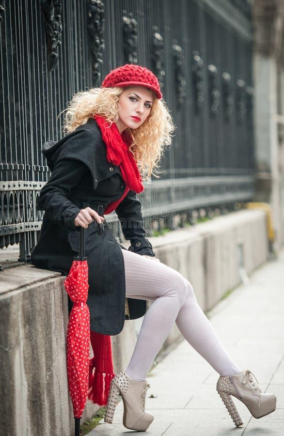 Jovem mulher atrativa em um tiro da fôrma do inverno. Rapariga bonita com o guarda-chuva vermelho na rua imagem de stock