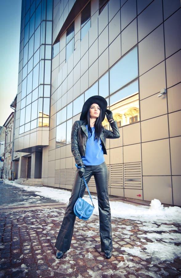 Jovem mulher atrativa em um tiro da forma do inverno Moça elegante bonita no couro preto com chapéu grande e a bolsa azul imagem de stock royalty free