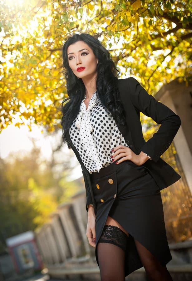 Jovem mulher atrativa em um tiro outonal da forma Senhora elegante bonita no equipamento preto e branco que levanta no parque fotos de stock royalty free
