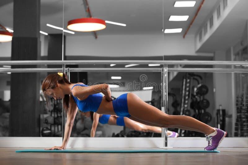 A jovem mulher atrativa está fazendo empurra levanta o exercício ao dar certo no gym fotografia de stock royalty free