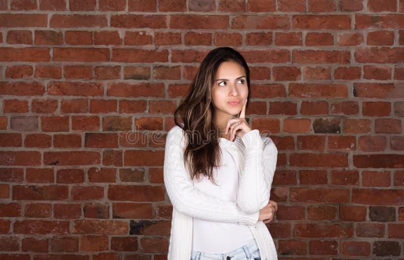 Jovem mulher atrativa na camiseta branca Para pensar sobre algo ou escolher fotos de stock royalty free