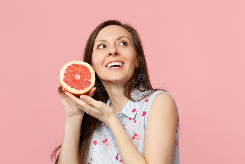 Jovem mulher atrativa na roupa do verão que olha mantendo a metade disponivel da toranja madura fresca isolada no rosa fotos de stock royalty free