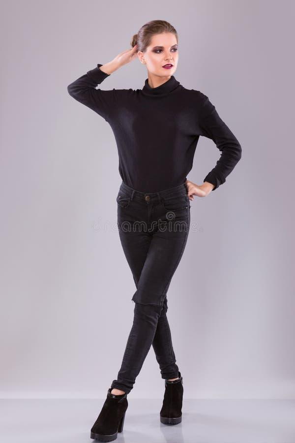 Jovem mulher atrativa no pulôver e em calças pretos sobre o fundo cinzento Composição brilhante fotos de stock royalty free