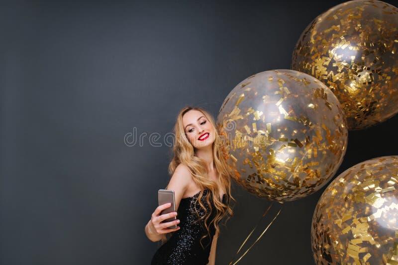 Jovem mulher atrativa no vestido luxuoso preto, com cabelo louro encaracolado longo, bordos vermelhos que tomam o selfie com balõ fotos de stock