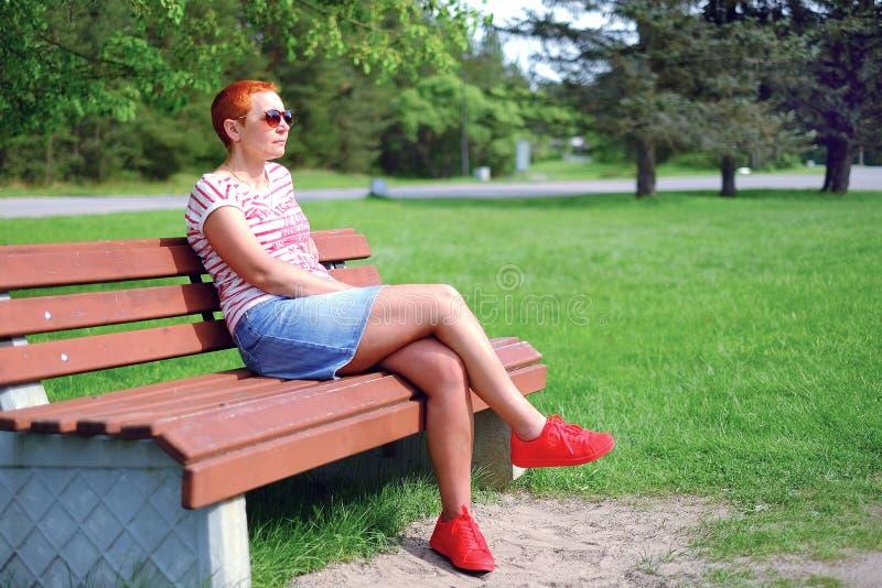 Jovem mulher atrativa nos vidros pretos, sentando-se em um parque do verão em um banco imagens de stock