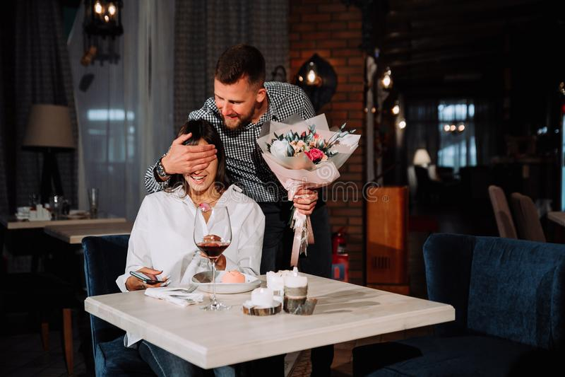 Jovem mulher atrativa obtendo flores de seu noivo ao sentar-se no café fotos de stock royalty free