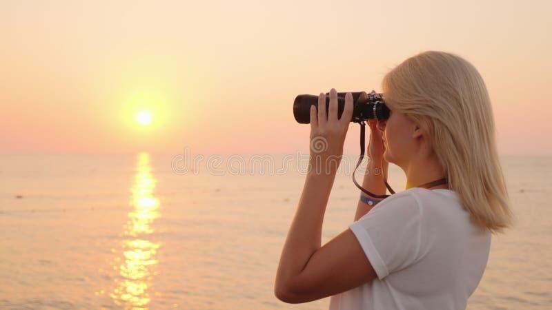 A jovem mulher atrativa olha através dos binóculos no nascer do sol sobre o mar Romance e aventura imagem de stock