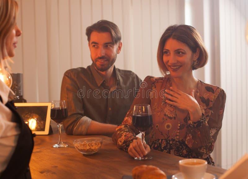 Jovem mulher atrativa que aprecia um vidro do vinho tinto ao falar ao barman foto de stock