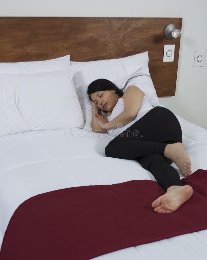 Jovem mulher atrativa que dorme bem na cama imagem de stock