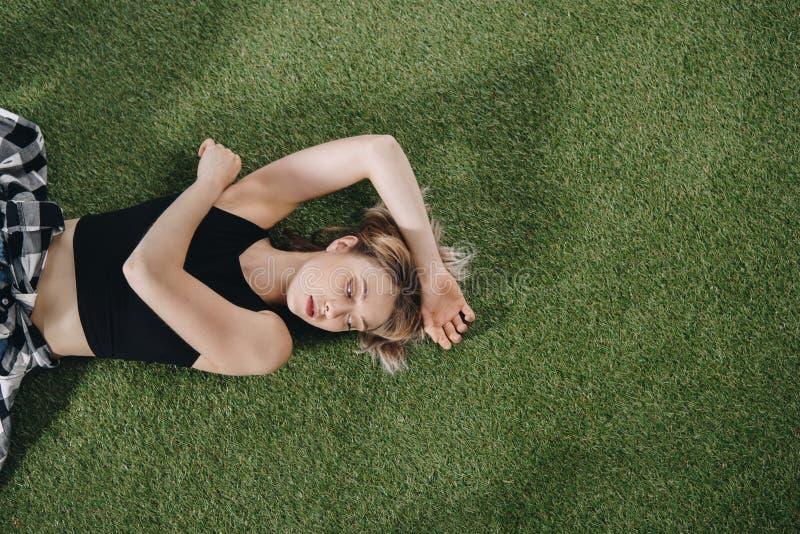 Jovem mulher atrativa que encontra-se na grama verde e que olha afastado fotografia de stock royalty free