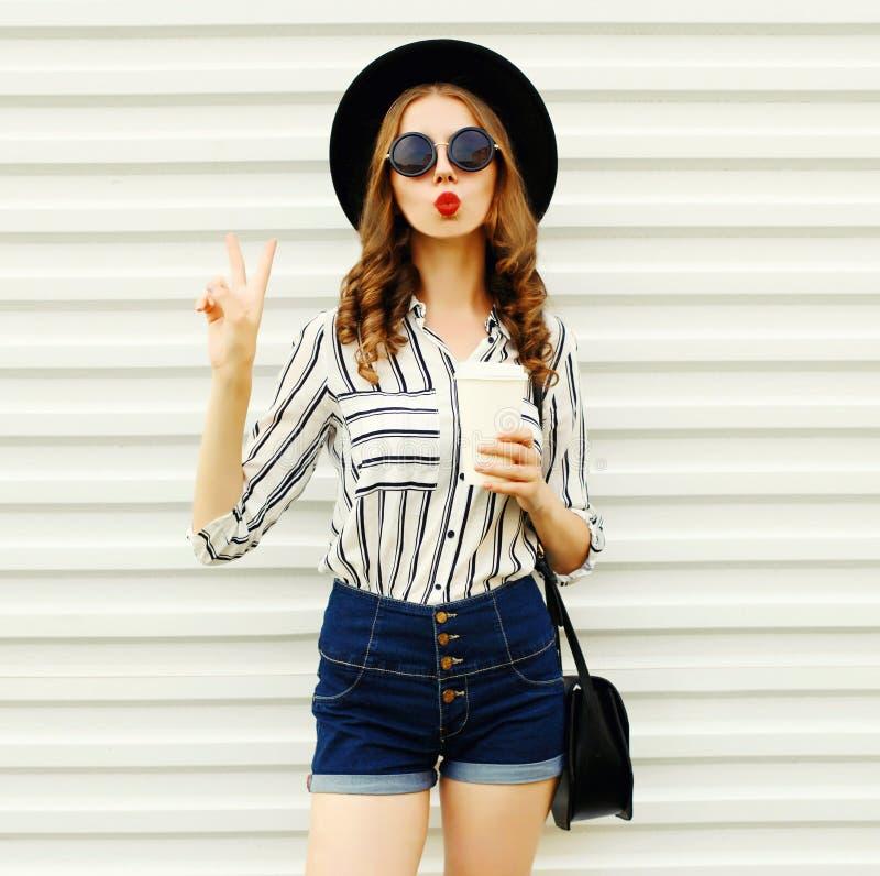 Jovem mulher atrativa que envia o beijo doce do ar que guarda o copo de café no chapéu redondo preto, short, camisa listrada bran foto de stock