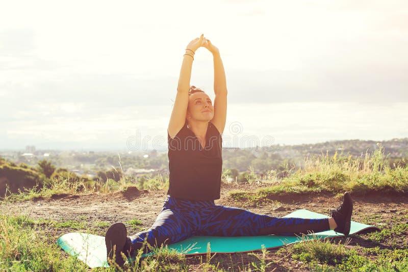 Jovem mulher atrativa que faz exercícios no monte sobre a cidade no por do sol imagens de stock