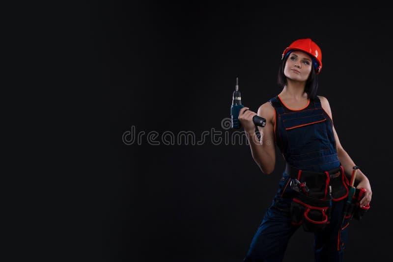 Jovem mulher atrativa que faz reparos no fundo preto Retrato de um trabalhador da construção fêmea Construção, conceito do reparo imagem de stock royalty free