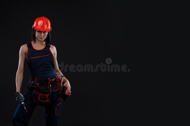 Jovem mulher atrativa que faz reparos no fundo preto Retrato de um trabalhador da construção fêmea Construção, conceito do reparo imagens de stock royalty free