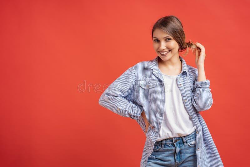 Jovem mulher atrativa que joga com seus cabelo e quando de sorriso que est?o contra o fundo vermelho fotografia de stock royalty free