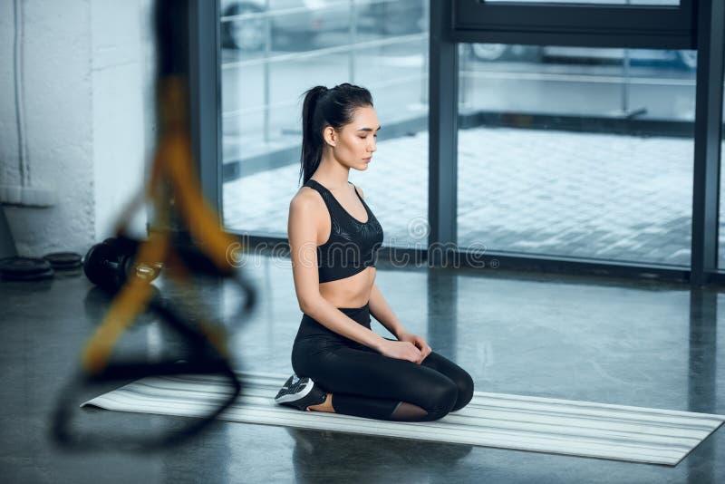 jovem mulher atrativa que maditating na esteira da ioga imagem de stock royalty free