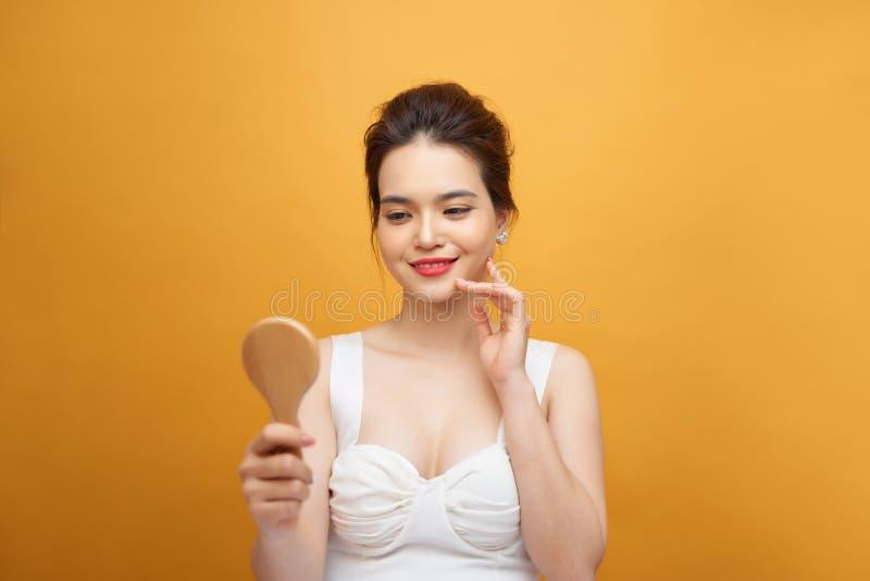 Jovem mulher atrativa que olha no espelho de mão no fundo amarelo imagem de stock royalty free