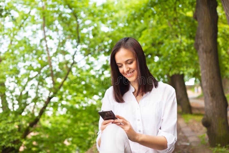 Jovem mulher atrativa que olha seus telefone e sorriso espertos fotografia de stock