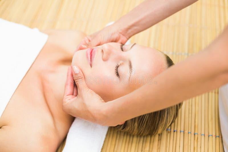 Jovem mulher atrativa que recebe a massagem facial no centro dos termas foto de stock