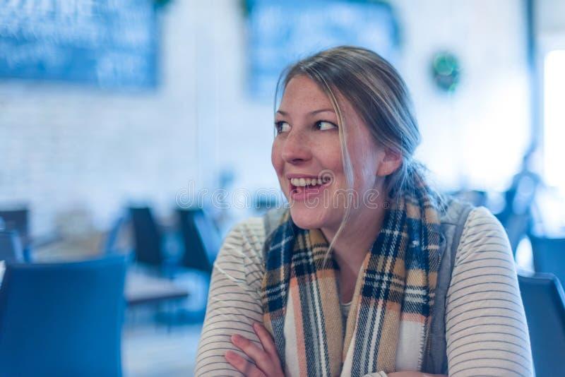 Jovem mulher atrativa que ri e que fala em um restaurante imagens de stock
