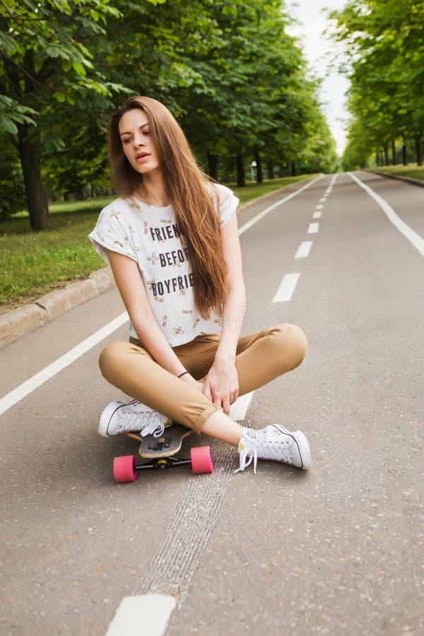 Jovem mulher atrativa que senta-se de pernas cruzadas em um longboard na estrada no parque skateboarding outdoors fotografia de stock