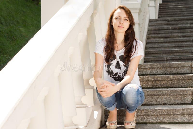 Jovem mulher atrativa que senta-se em etapas imagens de stock