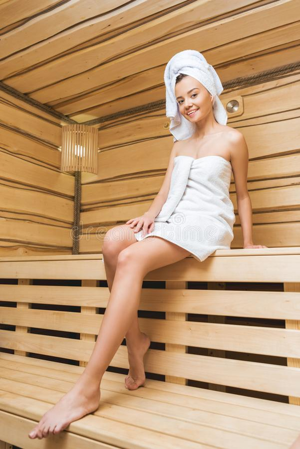 jovem mulher atrativa que senta-se na sauna coberta fotografia de stock royalty free