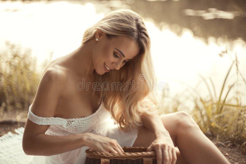 Jovem mulher atrativa que senta-se pelo lago no por do sol e que guarda a cesta do piquenique fotografia de stock royalty free
