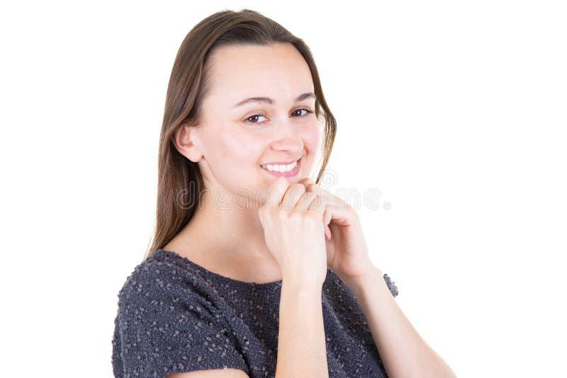 Jovem mulher atrativa que sorri descansando seu queixo em suas mãos foto de stock royalty free