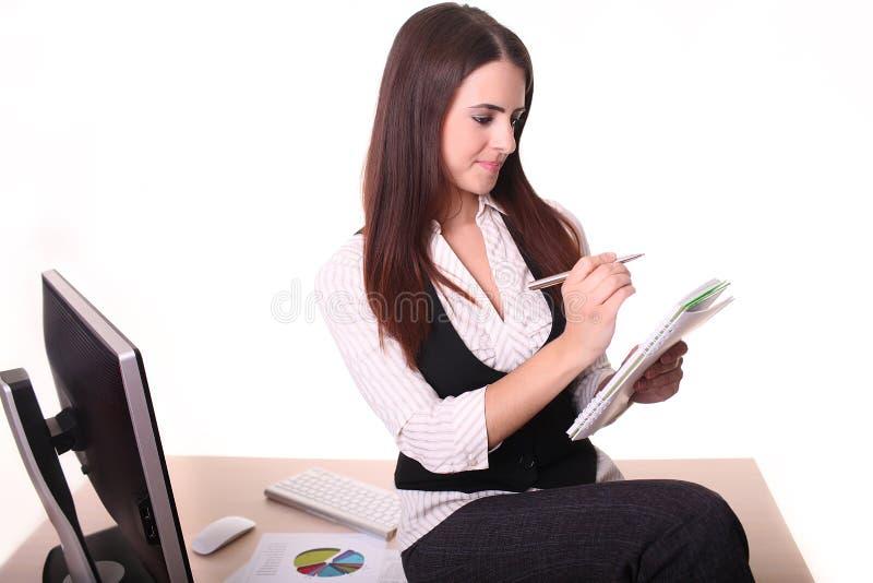 Jovem mulher atrativa que toma notas para não esquecer o somet imagens de stock royalty free