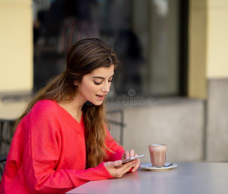 Jovem mulher atrativa que usa o app esperto do telefone celular em um terra?o da cafetaria fotografia de stock