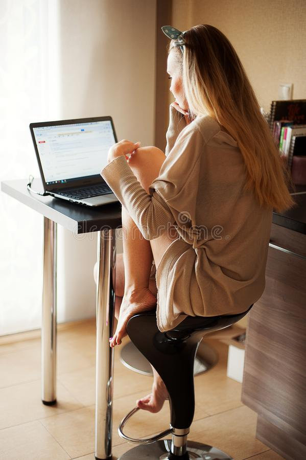Jovem mulher atrativa que usa o portátil ao relaxar em casa Tiro de atrás Estilo de vida no interior real fotos de stock royalty free