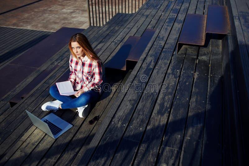 jovem mulher atrativa que usa o portátil que senta-se na escadaria de madeira que aprecia o dia ensolarado fora fotos de stock royalty free