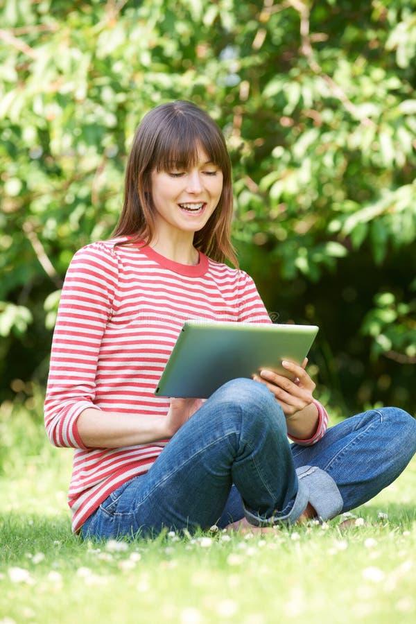 Jovem mulher atrativa que usa a tabuleta de Digitas no parque foto de stock royalty free
