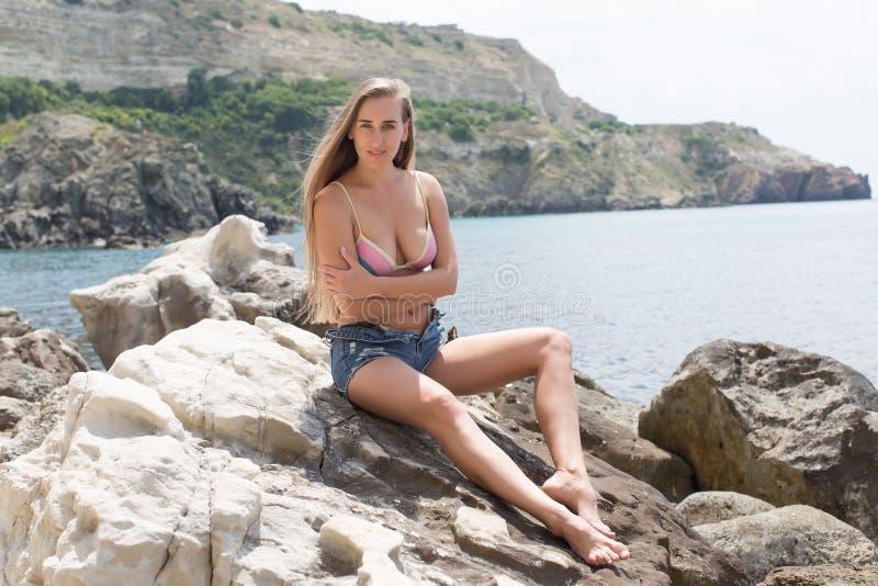 A jovem mulher atrativa senta-se no pedregulho litoral imagens de stock