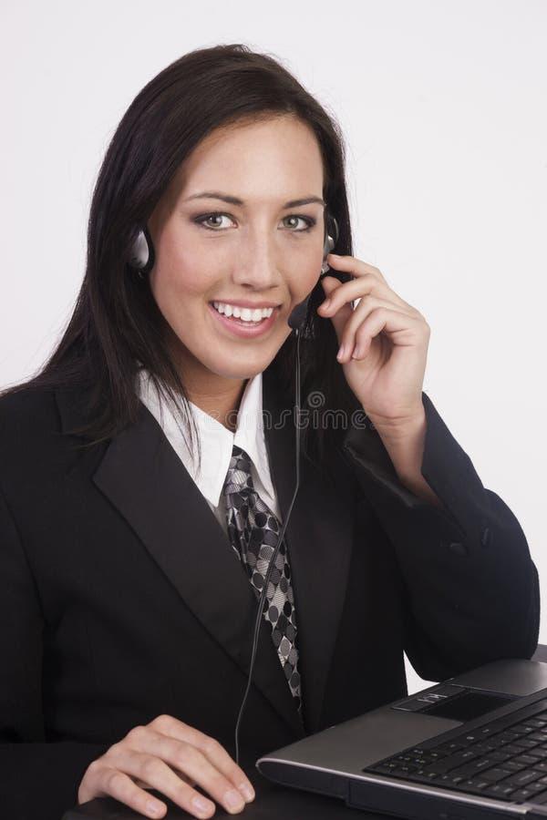 A jovem mulher atrativa trabalha auriculares do computador do serviço ao cliente imagens de stock royalty free