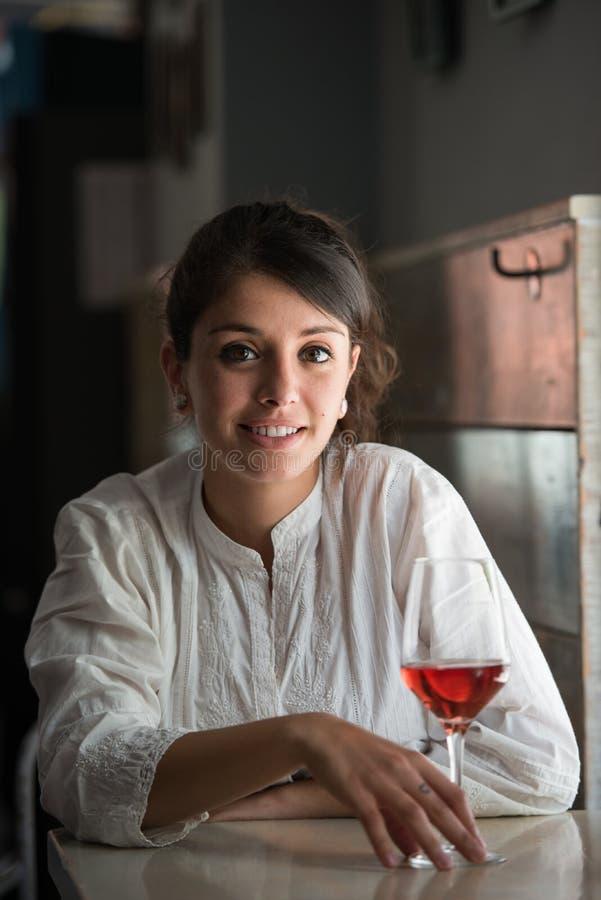 A jovem mulher bebe um vidro de vinho cor-de-rosa em uma situação de relaxamento em um restaurante foto de stock