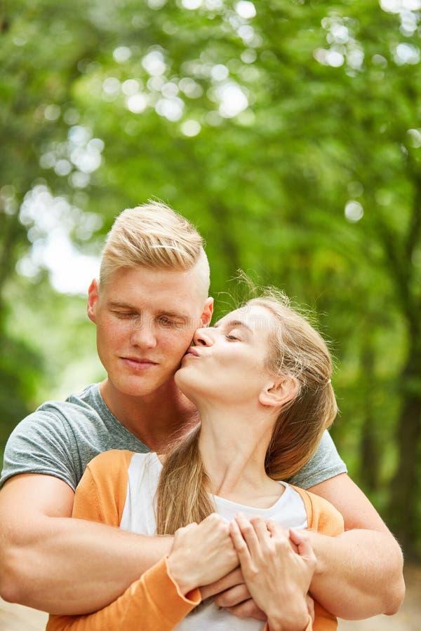 A jovem mulher beija seu sócio foto de stock royalty free