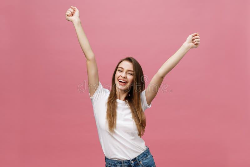 Jovem mulher bem sucedida feliz com sucesso do sorriso, da gritaria e da comemoração sobre o fundo cor-de-rosa fotos de stock