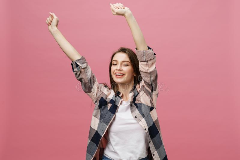 Jovem mulher bem sucedida feliz com sucesso do sorriso, da gritaria e da comemoração sobre o fundo cor-de-rosa imagem de stock royalty free