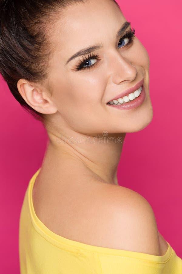 A jovem mulher bonita é de sorriso e de vista a câmera sobre o ombro fotos de stock royalty free