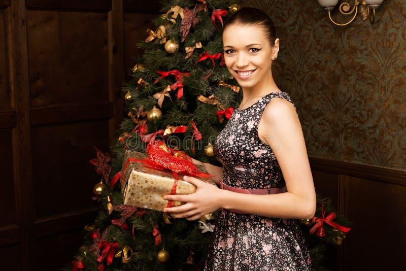 Jovem mulher bonita alegre com presente de Natal fotografia de stock
