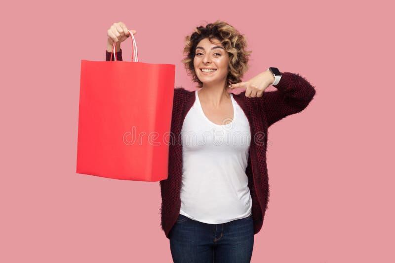 Jovem mulher bonita alegre na camisa azul com posição curlty do penteado e no dedo apontar aos sacos de compras e ao sorriso toot foto de stock royalty free