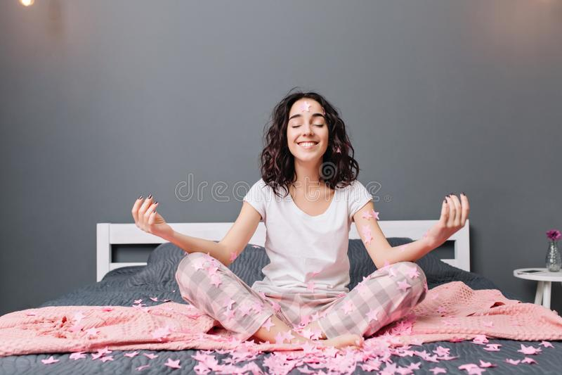 Jovem mulher bonita alegre nos pijamas com o cabelo moreno encaracolado que medita sobre a cama em ouropéis cor-de-rosa Sorriso m fotos de stock royalty free