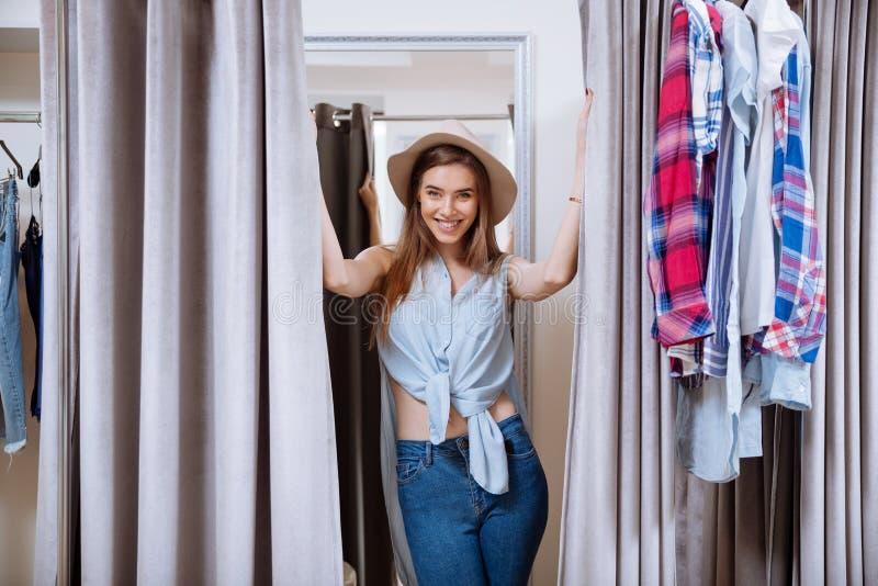 Jovem mulher bonita alegre que tenta na roupa em sala apropriada foto de stock royalty free