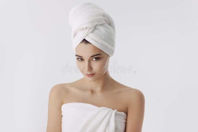 Jovem mulher bonita após o banho no fundo branco foto de stock